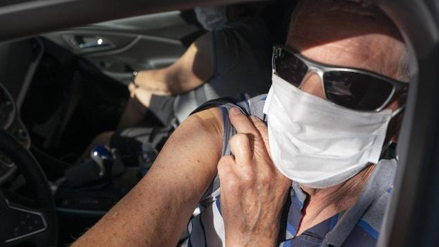 Un homme dans sa voiture et portant un masque montre l'endroit sur son épaule où il s'est fait vacciner.