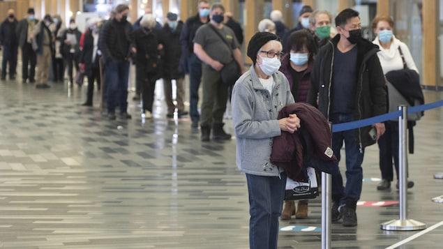 Une dame masquée au bout d'une longue file d'attente dans une clinique de vaccination.