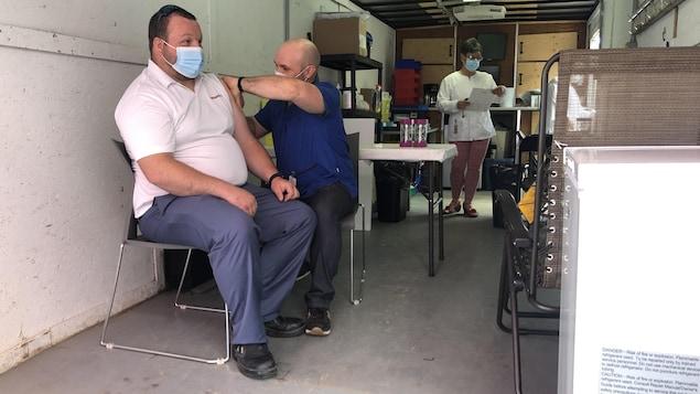 Un homme se fait vacciner contre la COVID-19 dans une clinique mobile.