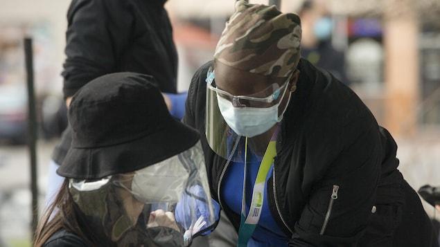 Une infirmière vaccinant une dame masquée derrière une visière.