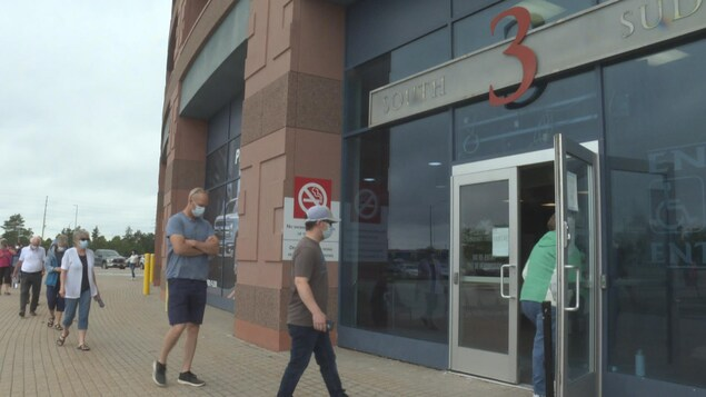 Des gens portant un masque entrent au Centre Canadian Tire pour se faire vacciner.