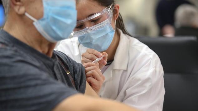 Une infirmière vaccine un homme.