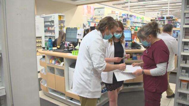 Un pharmacien discute avec un infirmière derrière le comptoir d'ne pharmacie.