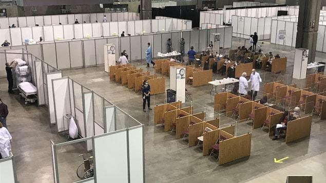Une vue en plongée montrant les aires d'attente et les cubicules de vaccination dans une immense clinique aménagée dans le Centre de foires d'ExpoCité.