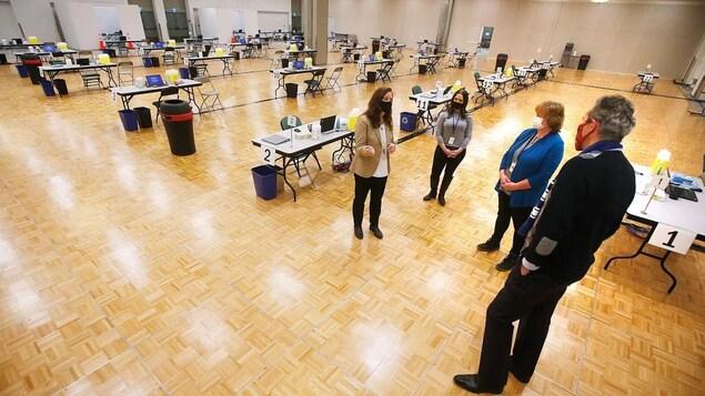 Brian Pallister, debout, en discussion avec des employées du Centre des congrès.