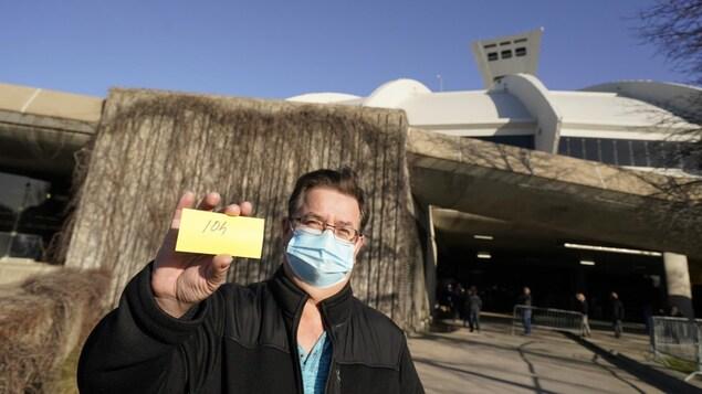 Un homme montre un coupon permettant de se faire vacciner.