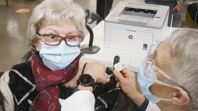 Une femme masquée lève les sourcils en se faisant vacciner.