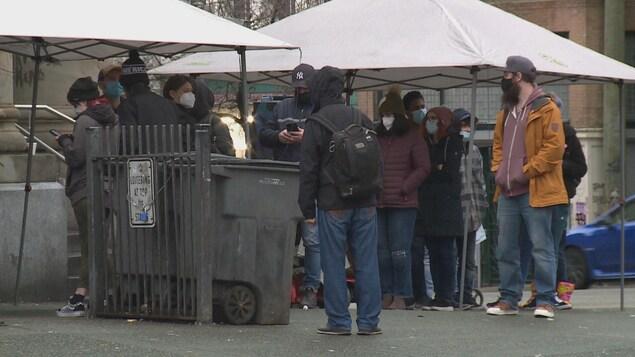 Une dizaine de personnes font la queue pour se faire vacciner contre la COVID-19.