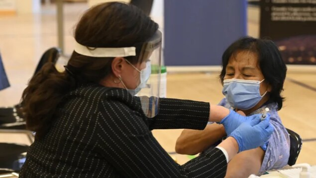 Tamara Dus, left, administers a first COVID-19 vaccine to personal support worker Anita Quidangen at a hospital in Toronto on Dec. 14, 2020.