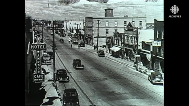 Centre-ville de Val-d'Or dans les années 30, avec des commerces et des voitures qui circulent.