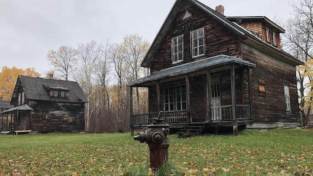 Une borne-fontaine se trouve devant une maison.
