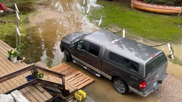 Un terrain et le perron d'une maison inondés par quelques centimètres d'eau.