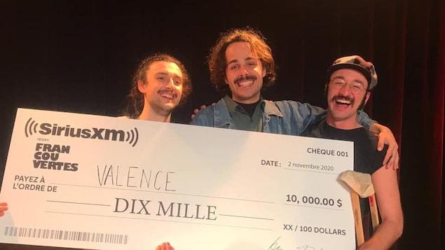Trois jeunes hommes tiennent un grand chèque de 10 000 $.