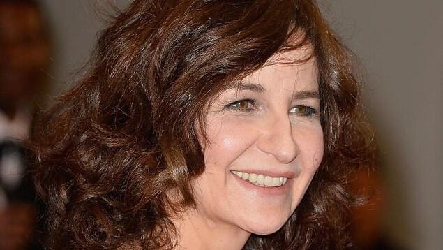 Portrait de Valérie Lemercier qui porte une robe de soirée noire.