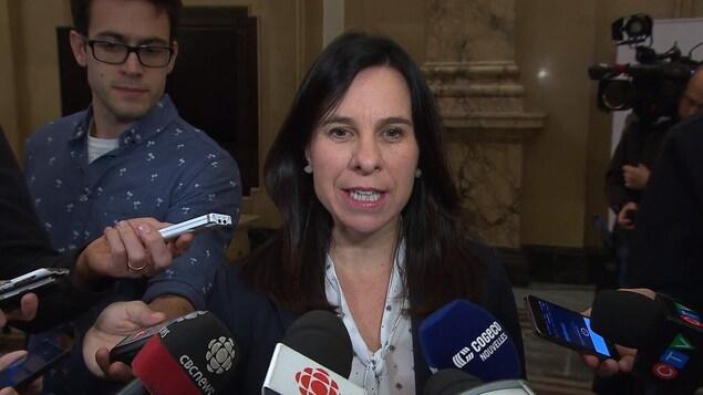 Valérie Plante est entourée de micros dans le hall de l'hôtel de ville de Montréal.