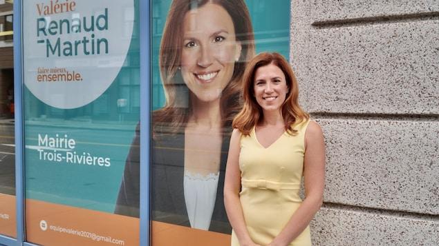 Valérie Renaud-Martin se tient devant son local de campagne électorale. Une photo d'elle est affichée dans la vitrine du local avec son slogan « Faire mieux ensemble ».