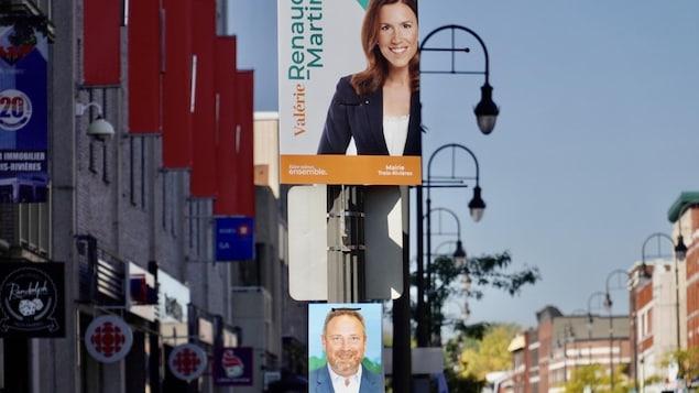 Les pancartes des deux candidats sur un même poteau au centre-ville de Trois-Rivières, près de la station de Radio-Canada.