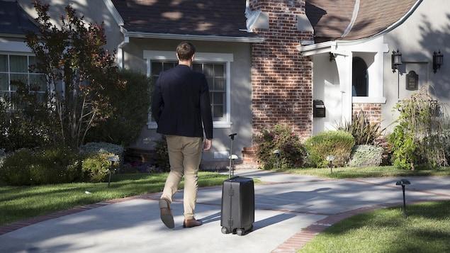 Un homme marche suivi par une valise qui avance toute seule.
