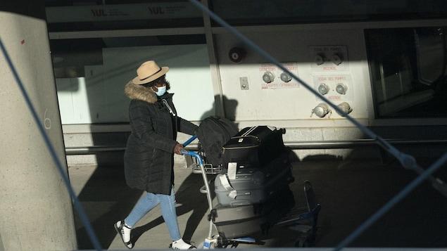 Une femme et ses valises à l'aéroport Montréal Trudeau le 29 décembre 2020.