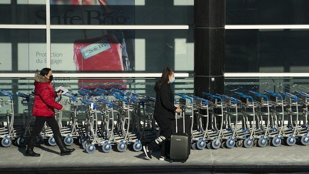 Deux femmes marchent à l'aéroport Montréal Trudeau avec leurs valises.