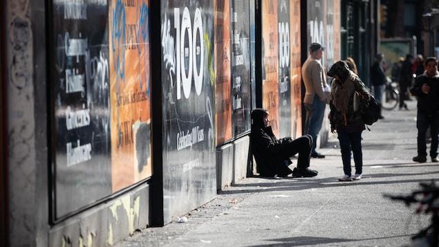 Des gens assis dans la rue dans le quartier Downtown Eastside, à Vancouver.