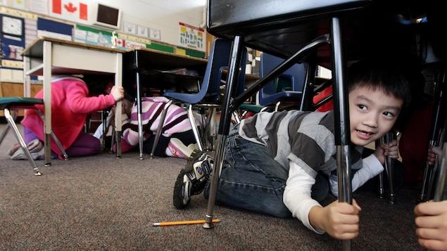 Un étudiant accroupi sous un bureau