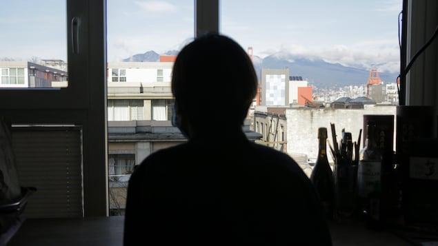 Une personne, dont l'identité est masquée par une ombre, est assise devant une fenêtre.