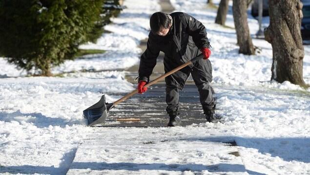 À Vancouver, un homme dégage un trottoir enneigé à l'aide d'une pelle.