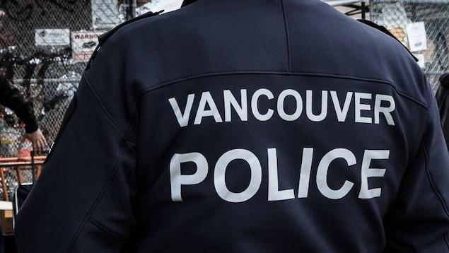 Un homme de dos porte un chandail sur lequel il est écrit Vancouver Police.