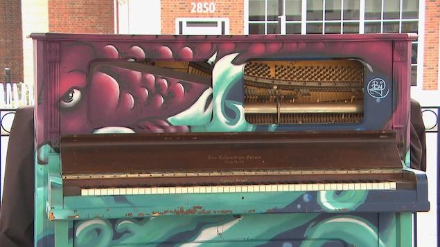 Un piano endommagé se trouve devant une bâtisse.