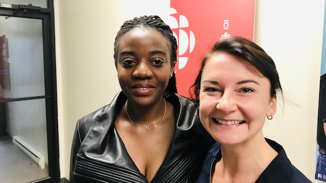 Deux femmes devant l'affiche de Radio-Canada.