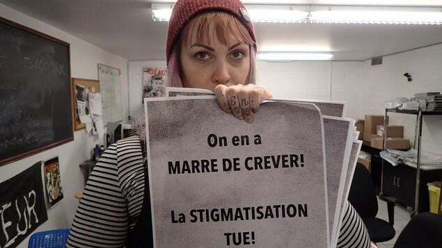 Vanessa Lefebvre Constantineau, rédactrice au journal « L'Injecteur », tient dans ses mains l'une des affiches de la campagne de sensibilisation qui se déroule en ce moment à Montréal. Sur l'affiche on peut lire: « On en a marre de crever! La STIGMATISATION TUE! »