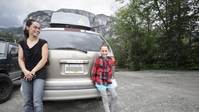Une femme et une jeune fille de 12 ans devant une fourgonnette grise, stationnée devant une montagne.
