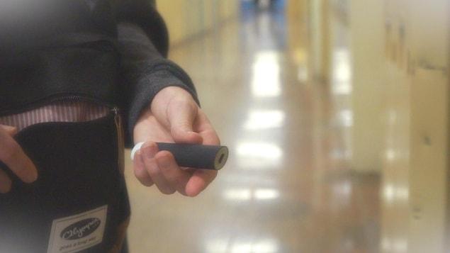 Une adolescente tient une cigarette électronique dans un corridor d'école.