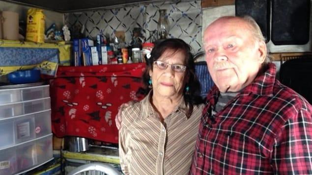 Le couple est debout dans la cuisine.