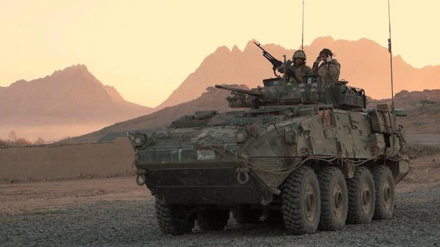Deux membres des Forces armées canadiennes à bord d'un véhicule d'assaut LAV dans un paysage aride.