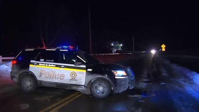 Un véhicule de la Sûreté du Québec est stationné en travers d'une route.