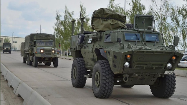 Un véhicule blindé et deux camions militaires sur la route