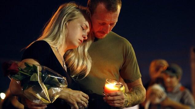 Deux personnes enlacées se recueillent. L'homme tient une bougie, la femme porte une rose.