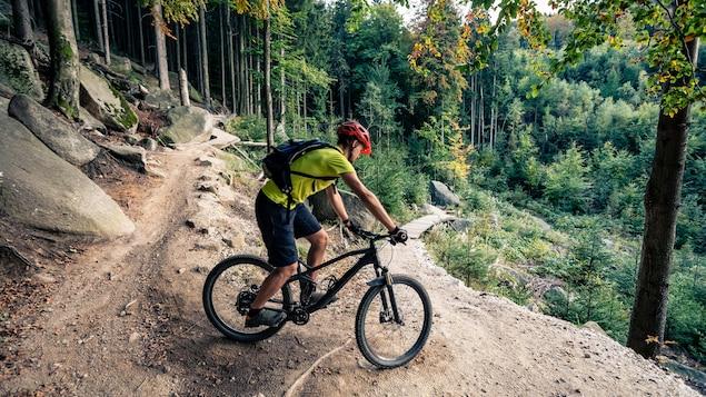 Un cycliste négocie une courbe sur une piste rocheuse en montagne.