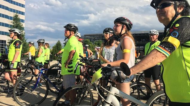 Des cyclistes qui écoutent un discours.