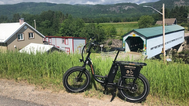 Un vélo électrique devant le pont couvert de l'Anse-Saint-Jean.