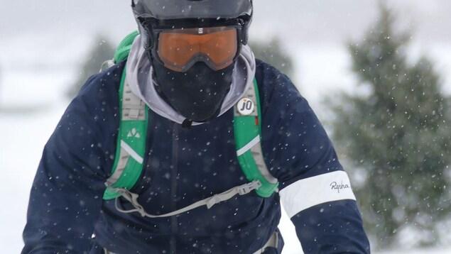 Un cycliste en plein hiver portant un casque et et des lunettes de ski.