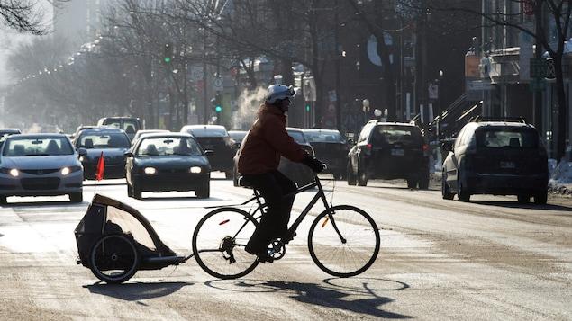 Une cycliste traversant une route occupée avec son bébé à l'arrière du vélo.