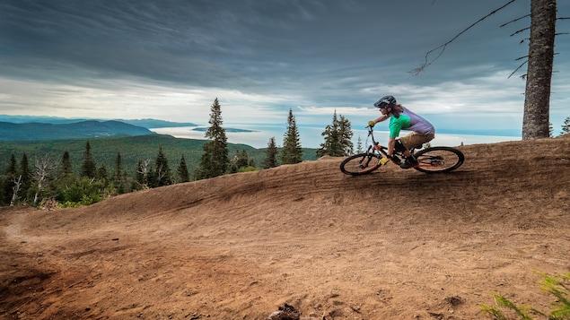 Une cycliste sur un sentier de vélo de montagne du Massif.