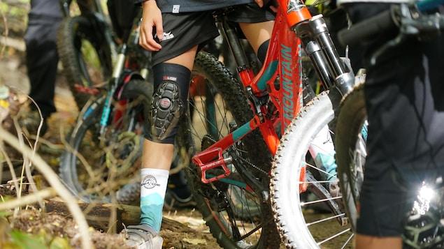 Un jeune assis sur son vélo de montagne parmi plusieurs autres.