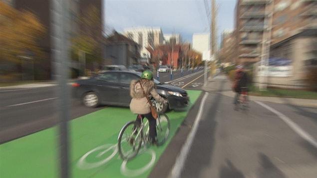 Une cycliste traverse une intersection à vélo.