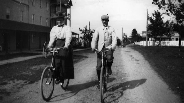 Un homme et une femme en costume d'époque à vélo