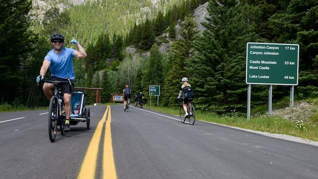 Un cycliste heureux de rouler sur une route sans voitures lève le poing dans les airs.
