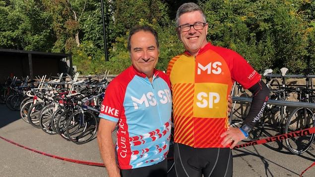 Les deux hommes sont en tenue sportive et posent devant plusieurs vélos.